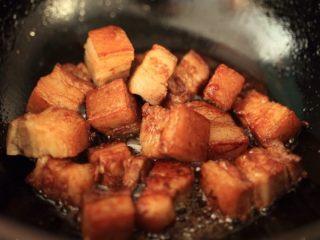 干笋烧肉,待冰糖起小泡放五花肉炒,炒糖色,放入蜂蜜、老抽,翻炒。