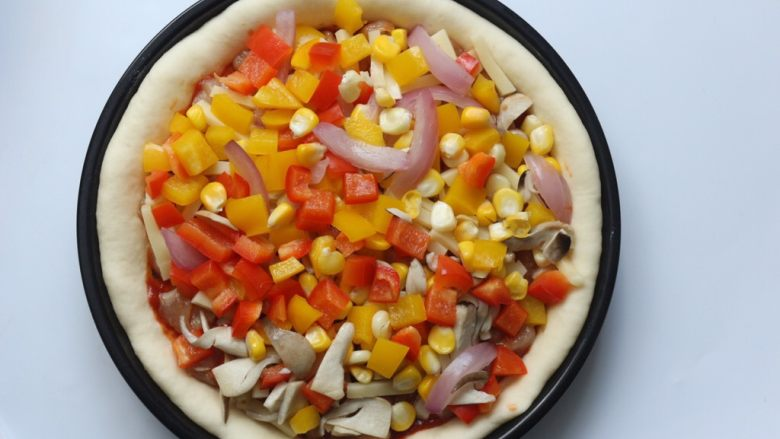 鸡肉蔬菜披萨,然后再撒100克芝士条,然后再把之前先蒸好的蔬菜铺在上面