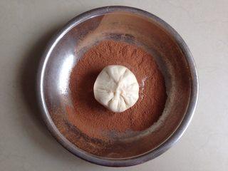 仿真蘑菇包,将光滑的一面放入到装有可可粉的盘里,使表面和侧面都沾上可可粉