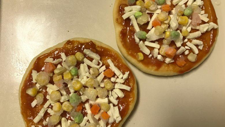 迷你香肠披萨,撒上适量的马苏里拉芝士再放一层蔬菜粒。