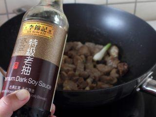 干豆角烧肉,9.炒出香味,排骨微焦黄,倒入适量的老抽。
