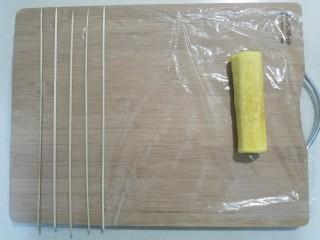 樱花玉子烧,案板上铺上保鲜膜,玉子烧放右边,左边均匀摆好竹签,竹签距离尽量保持一致。