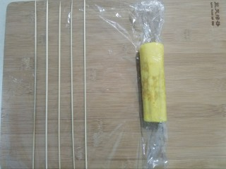 樱花玉子烧,保鲜膜包裹住玉子烧从左向右卷起