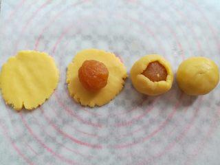 纯真凤梨酥,取一个酥皮按扁放上凤梨馅,用左手虎口位置包圆馅料收圆面团