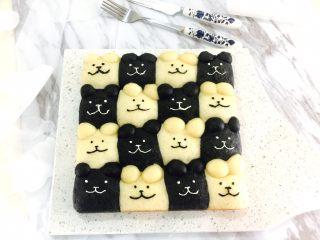 黑白小熊挤挤包,面包自然冷凉后,用原色奶油霜和加了竹炭粉的黑色奶油霜在面包挤出眼睛、嘴巴和鼻子。