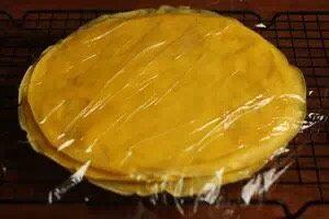 芒果班戟,把饼皮放在放凉架上散热,继续把剩下的面糊全部摊成饼皮。用保鲜膜盖住饼皮以免风干。