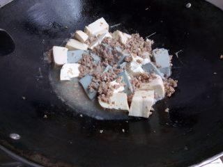 双色豆腐煮肉蓉,加入水,盖锅盖煮2、3分钟