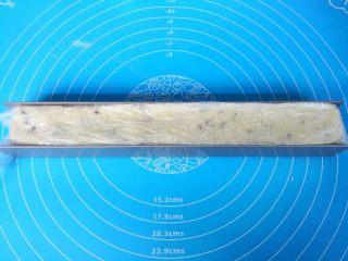 酸奶蔓越莓饼干,u形不粘饼干模具内铺上保鲜膜,把饼干面团用硅胶刀铲入模具内,表面整理平整。送入冰箱冷冻60分钟。