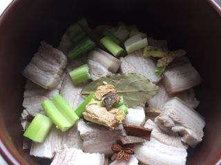笋干红烧肉,葱、姜、香叶、八角、桂皮铺在五花肉上,加入适量清水。 这个砂锅耗水量很少,清水放了不多,如果用炒菜锅之类的耗水量较大的锅清水要漫过五花肉。