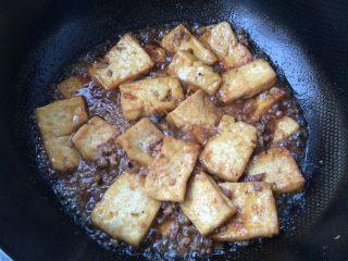 香煎豆腐,放入煎好的豆腐块,轻轻颠炒均匀,焖至汤汁快收干时,出锅装盘