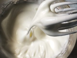 酸奶天使蛋糕,加入二分之一細砂糖,高速打發3-5分鐘,繼續加入剩余的細砂糖,將蛋白霜打到濕性發泡,六七分。提起打蛋器,蛋白霜半流動狀態,打蛋器頭上的蛋白霜拉起很長彎彎的尖勾。