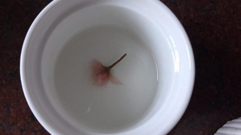樱花双色布丁,将煮好的白凉粉放入烤碗中,放入泡发后的樱花,用牙签挑出花型