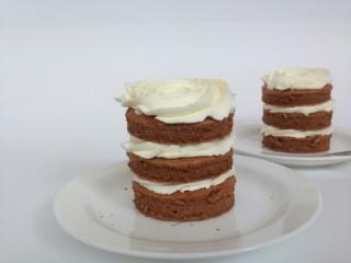 淋面可可蛋糕,300克淡奶油加25克糖,隔冰水打发,然后用裱花嘴在圆形蛋糕片上挤上奶油,三片为一组。
