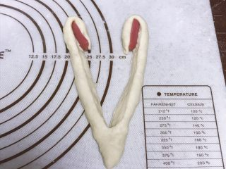 香葱芝士心形餐包,从中间切开,底部不要切断,将小热狗肠包裹在面团内侧