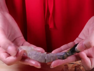 往虾里打入一颗蛋——虾扯蛋,记得在剥虾壳的时候,要留下虾尾哦,这样在烹饪的过程中虾尾卷起来,造型会更好看一些呢。还有就是记得要取出虾线。