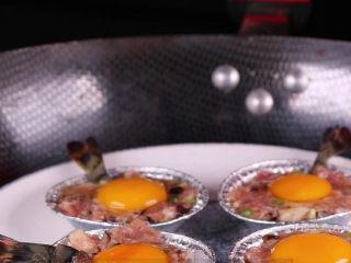 往虾里打入一颗蛋——虾扯蛋,接着将做好了的虾扯蛋装入盘中下锅隔水蒸。