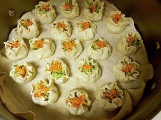 素烧卖,依次完成所有后摆放在蒸锅中,上面放些胡萝卜碎。