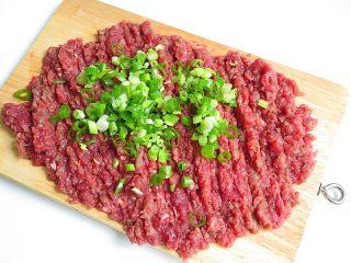 羊肉煎饺,羊肉切成大块后剁成肉泥,再加入葱碎,滴几滴油继续剁,细腻即可
