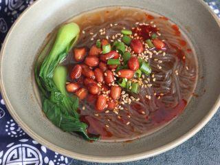 美味酸辣粉,煮好的红薯粉捞入碗中,放入油炸花生米、小油菜,葱花碎、撒一勺芝麻,淋上调好的料汁,再浇上煮红薯粉的汤即可。