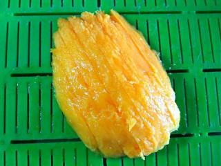 低脂养颜思慕雪,芒果切出一半的果肉,去皮,切细条