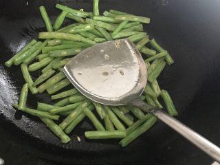 四季豆烧茄子,下入四季豆,并用锅铲按压,煸炒