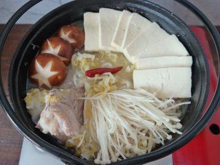 酸菜炖大骨棒,然后放上 蘑菇 豆腐 金针菇 继续煮一会儿就行