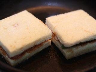 墨西哥香肠三明治,放上三明治,用锅产等重物压在上方,使其能更好煎入味.3分钟左右翻面,再次煎另一面即可.