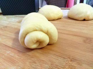 全蛋吐司,把面团反一下面,把面团擀成舌头状。将面团从上往下卷。