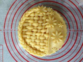 编织苹果派,刚出一块小的派皮,铺在三分之一处,去掉多余的派皮。用花型模具压出大小花朵放在上面