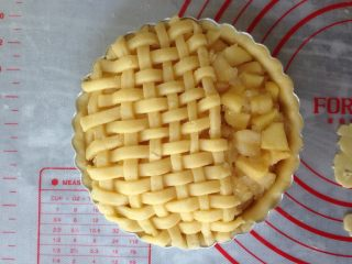 编织苹果派,将苹果馅放进去,尽量铺满,将编织好井字形的放在上面,切出多余的部分,留出三分之一位置。