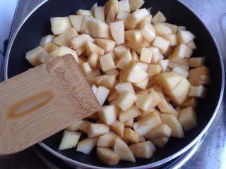 编织苹果派,在等待冷藏的时间,可以做苹果馅。锅里加入10克黄油,黄油溶化之后,加入加入苹果丁翻炒一下,全程用小火。