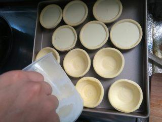 烘焙小白零失败的——黄桃蛋挞,搅拌均匀后倒入蛋挞皮内,每个七八分满即可。