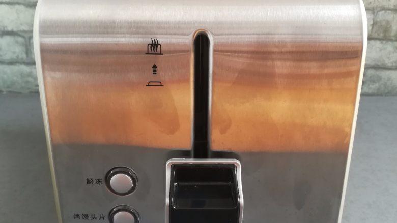 培根芝士三明治,面包片放入多士炉里二档烤一分钟,烤好后自动弹出
