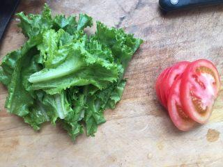 至珍全虾堡,烤虾的时候我们可以把生菜洗一洗,撕成小瓣;西红柿洗一洗,切成薄片。