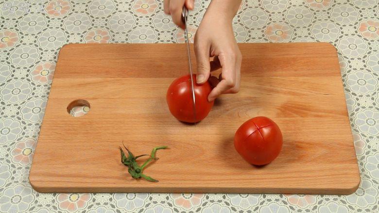 西红柿炒蛋,西红柿去蒂,在底部轻轻的划十字刀。