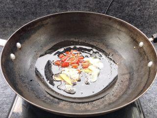酱爆鱿鱼花,锅中倒入适量猪油,放入大蒜、姜,泡椒,花椒爆香。为什么要放猪油呢!用猪油炒鱿鱼更香,不相信你可以试试哦!