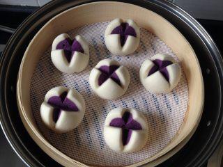 紫薯开花馒头,这是醒发好的馒头坯子,口会张开一些;盖上盖子,中火蒸制约15分钟,焖3分钟才可开盖