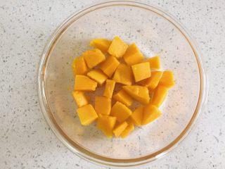 芒果牛奶布丁,切成小块的芒果放入耐冷的容器中,铺在容器最底部