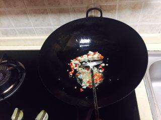 神下饭之酸苦瓜炒卤肥肠,再加少许油加热,倒入小米椒碎和蒜末炒香。
