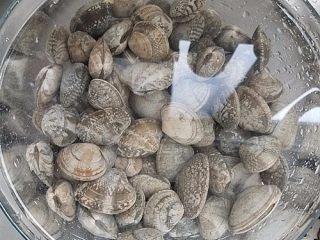 黄酒蛤蜊,先把买回来的花蛤蜊用盐水浸泡,滴一滴植物油,让蛤蜊把沙吐干净。
