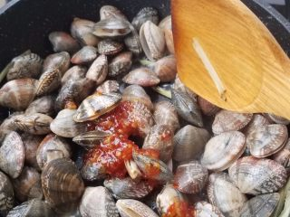 黄酒蛤蜊,简单翻炒几下后加入辣酱,再次炒几下。