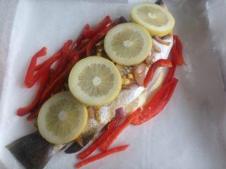 柠檬烤鱼,再放上柠檬片和红椒丝,用油纸和锡纸包好。
