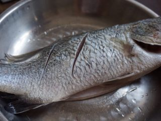 柠檬烤鱼,鲈鱼去鳞去内脏,洗净,在两侧鱼身上斜切三刀