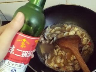 香辣爆炒花甲,倒入适量白酒,白酒倒入最好是在放入花甲汤之后,不然火头大了锅里容易起火。或者花甲和汤一起入锅后再放各种调料