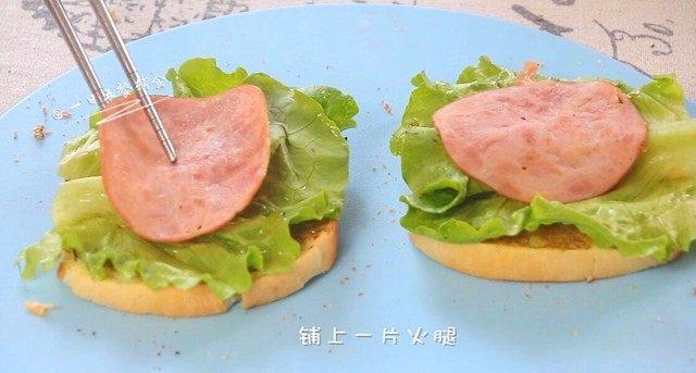 牛油果鸡蛋火腿三明治,铺上一片生菜叶。再铺上一片火腿。