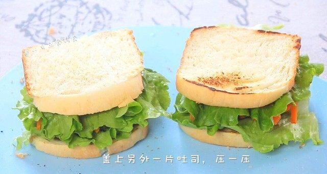 牛油果鸡蛋火腿三明治,如果还有火腿再铺一片,再铺上一层生菜。另外一片吐司再抹上一层坚果酱。坚果酱不仅营养更丰富,也使三明治上升了口感,吐司片盖上,压一压。