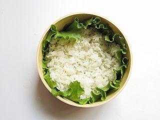 兔子趣味便当,消毒过的便当盒用生菜叶铺好,放入少量米饭摊开铺好