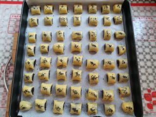枣泥一口酥,所有的枣泥酥放入垫了油纸的烤盘里,刷上一层薄薄的蛋液,撒上适量的芝麻