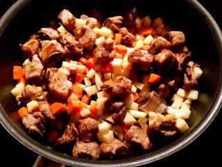土豆排骨焖饭,排骨被煎到两面金黄以后,放入葱白,姜碎,蒜粒,料酒,蚝油,酱油,盐,白糖翻炒。调料炒匀以后,倒入胡萝卜丁和土豆丁翻炒5分钟,如果觉得干,可以适量加2勺水。
