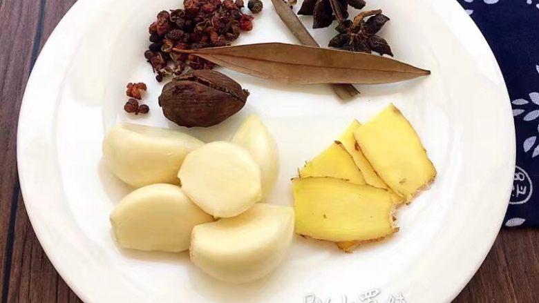 红烧肥肠,草果用刀切开,姜切片,三个大蒜全部剥皮备用。